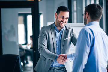 Two smiling businessmen shaking hands while standing in an office.