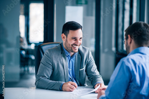 Принти на полотні Handsome male client signing document on a meeting with real estate agent