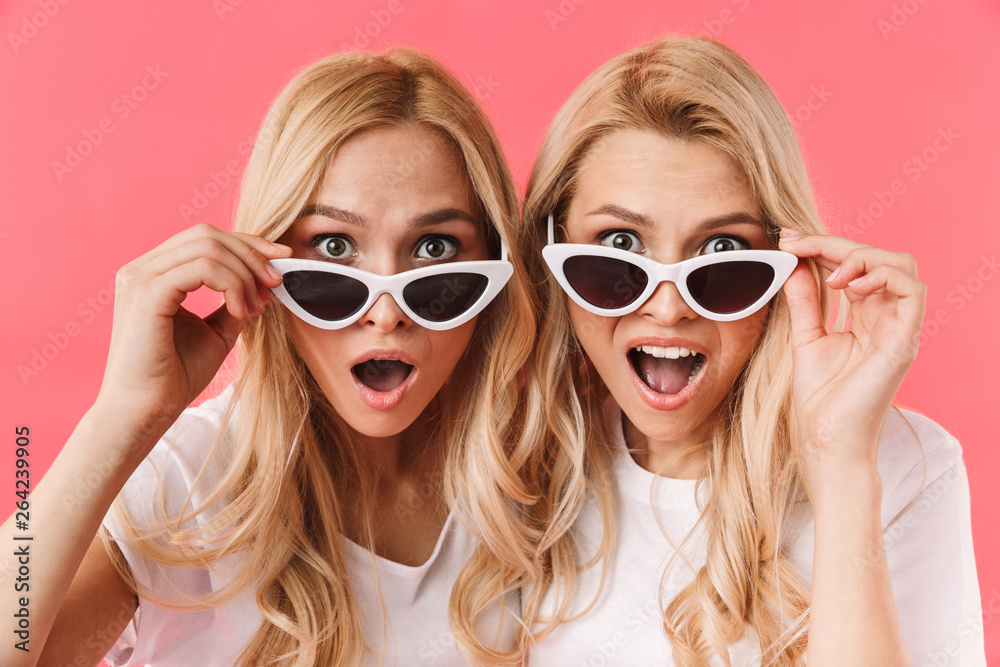 Fototapeta Shocked blonde twins take off sunglasses and looking at camera