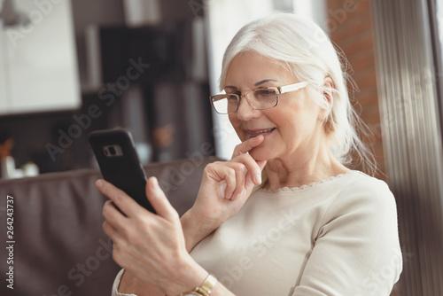 Foto  Beautiful senior woman texting at home