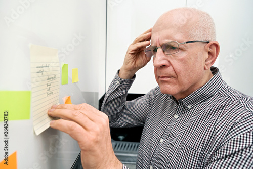 Fotografie, Obraz Elderly man with dementia looking at notes