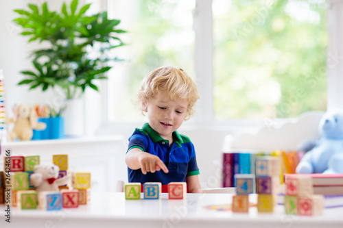 Photo Child learning letters. Kid with wooden abc blocks
