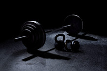 BACK LIT 365 Pound Weight On Barbell With Kettle Bells On Floor With Dramatic Light In Gym