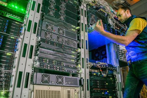 A system technician installs a new server. The engineer performs work on the replacement of computer equipment in the data center. Specialist maintains a modern hosting site.