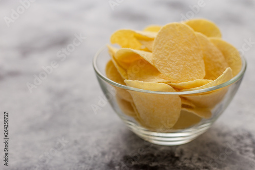 Fotografie, Obraz  Potato chips in glass bowl.The concept of fast food .