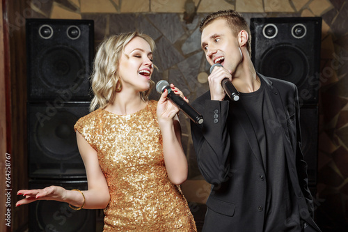 Portrait of a happy young couple with microphones and glasses in a karaoke bar Fototapeta