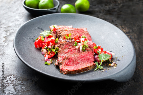 Leinwand Poster Traditional South American barbecue wagyu roast beef sliced with pico de gallo a