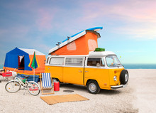 A Classic Yellow T2 Caravan Camper Van On The Beach, Family Camp Site With Tent, Bicycle, Surf Board And Other Entertainment. Nostalgic Mood.
