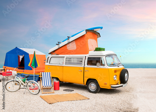 Poster Vintage voitures A classic yellow VW T2 caravan camper van on the beach, family camp site with tent, bicycle, surf board and other entertainment. Nostalgic mood.
