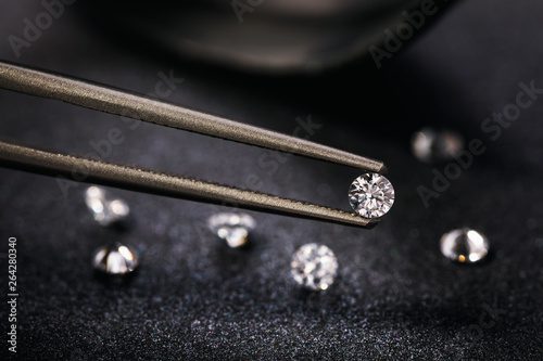 Gemstone clamped in tweezers. Jewelry inserts close-up - 264280340