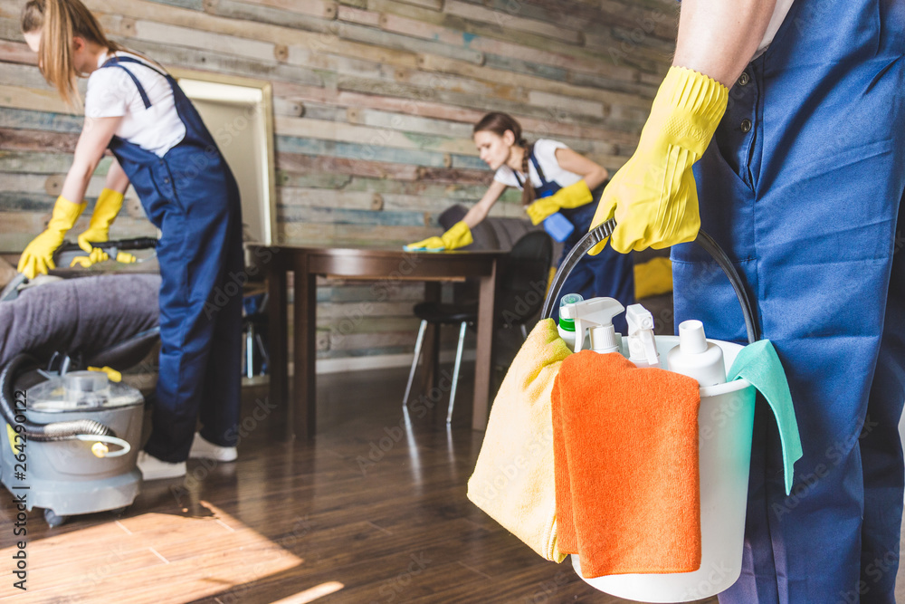 Fototapeta Cleaning service with professional equipment during work. professional kitchenette cleaning, sofa dry cleaning, window and floor washing. man and women in uniform, overalls and rubber gloves