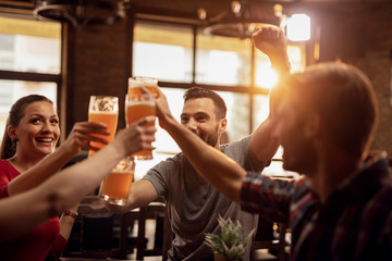 Group of cheerful friends toasting with beer in a bar.