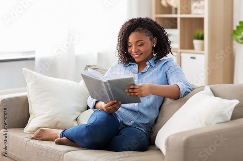 leisure, literature and people concept - smiling african american woman reading Canvas-taulu