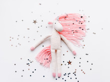 Cute Fairy Unicorn With A Pink Mane And A Tail Made Of Threads. Crocheted Hand Made Toy On White Background With Silver Stars Confetti. Trendy Creature, Symbol Of Magic And Miracles.