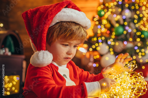 Fotografie, Obraz  Happy little kid is playing with Christmas light on Christmas tree background