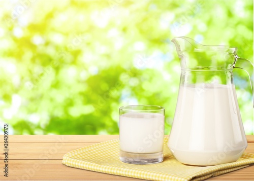 Glass of milk and jar on table