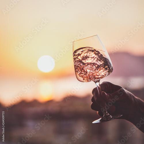 Glass of rose wine in mans hand with sea and sunset at background, close-up, square crop. Summer evening relaxed mood concept Fototapete
