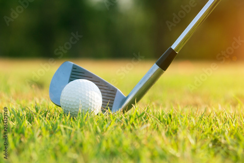 Deurstickers Golf Golf clubs and golf balls on a green lawn in a beautiful golf course