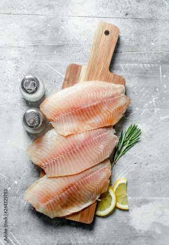 Fish fillet on a wooden cutting Board with rosemary, spices and lemon slices Fototapeta