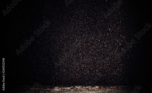 selective focus of golden sparkles falling on white table isolated on black Canvas-taulu