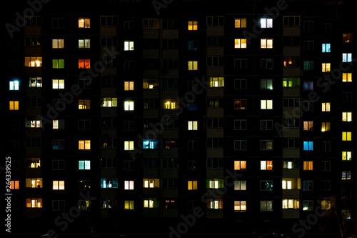 Night time lapse of Light in the windows of a multistory building. life in a big city