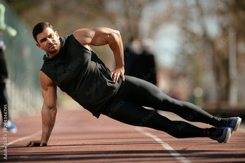 Fototapety, obrazy: Athlete warming up. Man doing plank. Guy warming up before a workout.