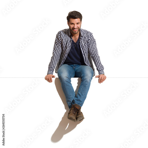 Obraz Smiling Handsome Man Is Sitting On A Top Of White Banner - fototapety do salonu