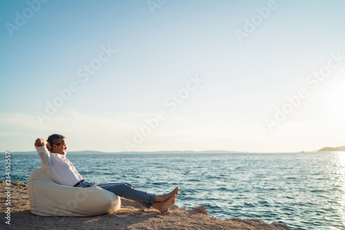 Senior man lying on deck chair on the beach during sunset Fototapet