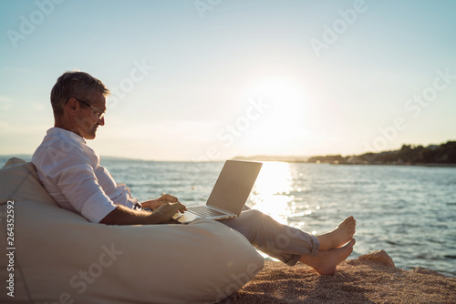 Fotomural Senior man working on his laptop lying on deck chair on the beach during sunset