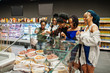 Group of five african womans buying meat dishes in supermarket.