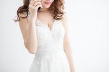 白背景に白いレースのドレスを着た美脚の女性が携帯電話を持っているモデル美人綺麗キャバクラキャバ嬢