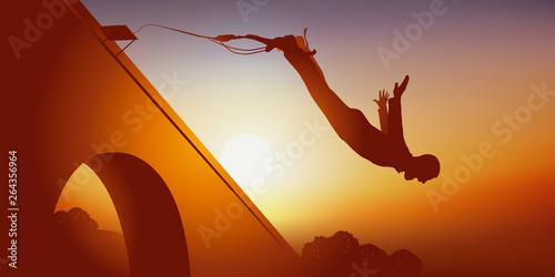 Un homme aimant le sport extrême et les émotions fortes, se jette du haut d'un pont attaché à un élastique Fototapeta