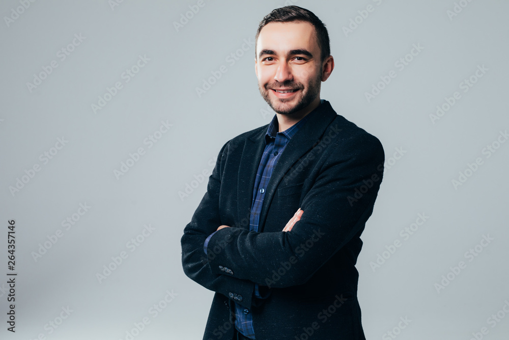 Fototapety, obrazy: Smiling businessman standing with arms folded isolated on a white background