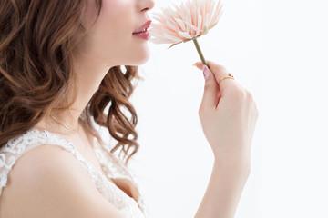 白背景に茶髪の巻き髪をした綺麗な女性が花をもって上を向いている姿キャバクラモデル美人