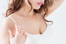 白背景に巻き髪の茶髪の綺麗な女性が朝のタンクトップ姿ヨガストレッチ