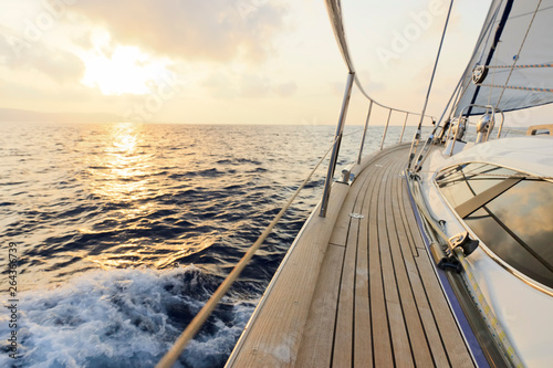 Yacht sailing towards the sunset Fototapeta