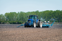 A Large Blue Tractor Prepares The Land For Planting
