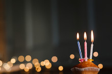 Three Multicolored Candles In The Cake, Burning Candles On The Table Against The Background Of A Garland Of Lights With Space For Text. Concept For The Day Of Birth, 3 Years, Greeting Card
