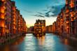 Leinwanddruck Bild The Warehouse district Speicherstadt during twilight sunset in Hamburg, Germany. Illuminated warehouses in Hafencity quarter in Hamburg.