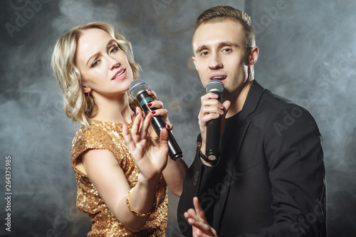 Obraz na płótnie Portrait of a young couple with microphones on a dark background