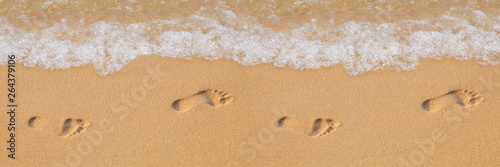 Obraz Texture background Footprints of human feet on the sand near the water on the beach - fototapety do salonu