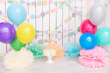 Photo Zone With Paper Garlands, Balloons, Paper Balls, Pom Poms, Confetti And Cream Cake. Birthday Cake. Smash Cake. One Year. Pink, White, Blue, Green, Yellow Colors. Rainbow