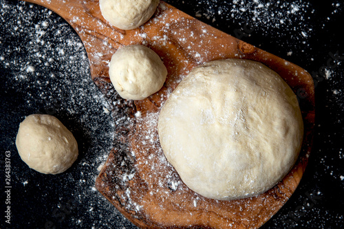 Dough for bread or pizza on a board. Black background