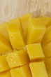 The mango fruit is cut into pieces lying on a wooden plank on a linen tablecloth