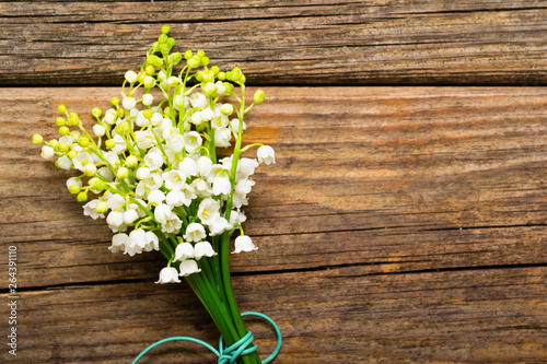 Photo Stands Lily of the valley bunch of lily of the valley flowers on old weathered wooden table, directly above