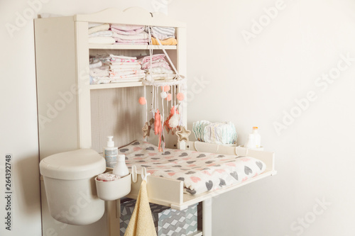 Baby changing table in light bedroom Wallpaper Mural