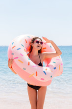 Enjoying Suntan And Vacation. Portrait Of A Happy Girl Looking Through Inflatable Ring Stay On The Sea Beach. Summer Holidays Concept
