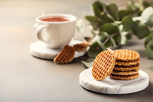 Mini Stroopwafel, Syrupwaffles Cookies With Cup Of Tea And Eucalyptus Twigs On Light Background With Copy Space.