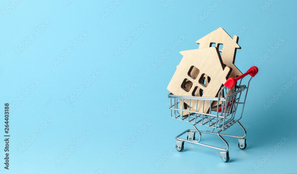 Fototapeta Shopping cart and house on a blue background. Buying and selling real estate. Copy space for text.