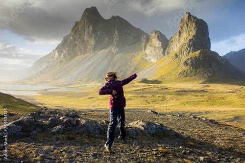 Aluminium Prints Black Happy joyful girl with long and dark hair jumping on nature in a outdoor hiking trip against the background of huge pointed, peaked mountains in eastern Iceland near the coast of the Atlantic Ocean.